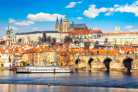 Prague Castle, Charles bridge, Mala Strana district and sightseeing touristic ship during summer sunny day in Prague, Czech Republic