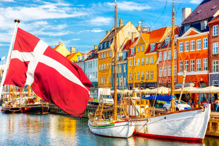 Copenhagen iconic view. Famous old Nyhavn port in the center of Copenhagen, Denmark during summer sunny day with Denmark flag on the foreground Banque d'images