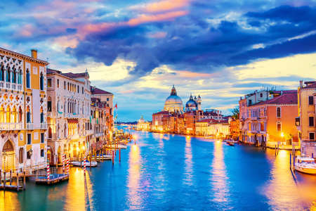 Basilica Santa Maria della Salute, Punta della Dogona and Grand Canal at blue hour sunset in Venice, Italy with boats and reflections