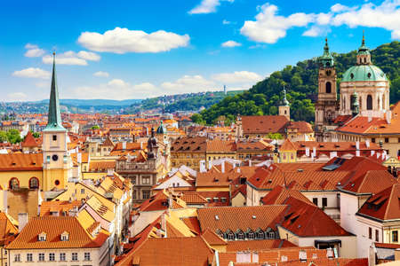 Beautiful sunny day cityscape of Prague with cathedral of St. Nicholas and red roofs houses.