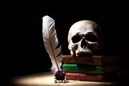 Drama or theater and literature concept. Old inkstand with feather near skull on books against black background. Dramatic light.