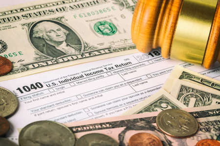 Closeup image of american 1040 Individual Income Tax return form with american dollar money, coins and judge gavel