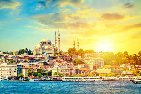 Touristic sightseeing ships in Golden Horn bay of Istanbul and view on Suleymaniye mosque with Sultanahmet district against beatiful sunset