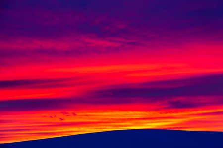 Vivid saturated beautiful sunset sky in pink, purple and blue colors with a mountain. Sunset background Archivio Fotografico