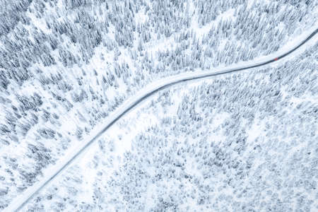 Aerial drone view of road in winter forest with red car.