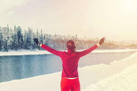 Hiker girl in red standing near river against winter forest and mountains. Travel concept Archivio Fotografico