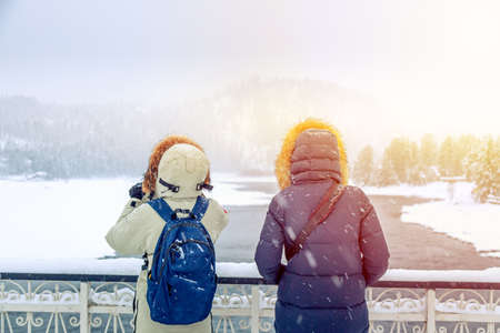 Hiker girls in down jackets standing near river against winter forest and mountains. Travel concept Archivio Fotografico