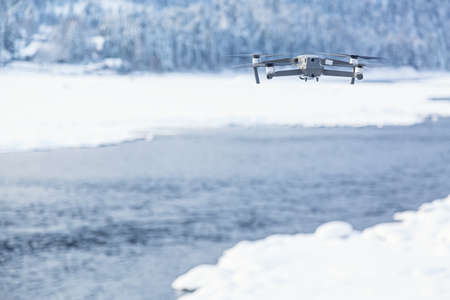 Flying drone against winter background with river and forest. Archivio Fotografico