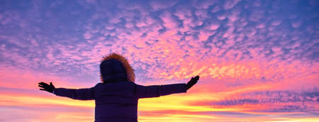 Hiker girl in down jacket standing against amazing colorful sunset. Travel concept
