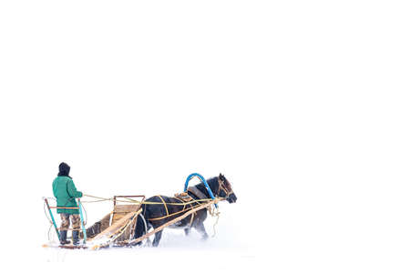 Man in a hood with old sledge pulled by beautiful black horse in winter