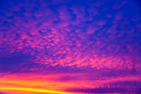 Vivid saturated beautiful sunset sky in pink, purple and blue colors. Abstract amazing sunset background. Archivio Fotografico