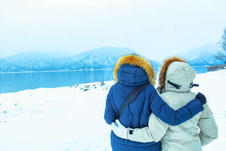 LGBT travel concept. Hugged hiker girls in down jackets standing near lake and mountains in winter. Archivio Fotografico