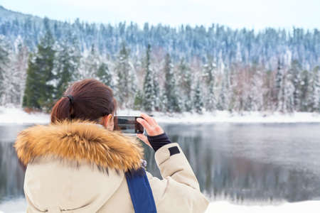 Young hiker girl with in down jacket making photos of river and forest in winter. Travel concept Archivio Fotografico