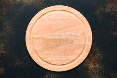 New round wooden cutting board for pizza on stone background. Top view. Mock up for food project