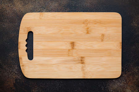 New rectangular bamboo wooden cutting board on stone background. Top view. Mock up for food project