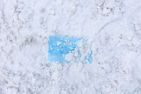 Blue medical protective mask on white snow. Top view. Archivio Fotografico
