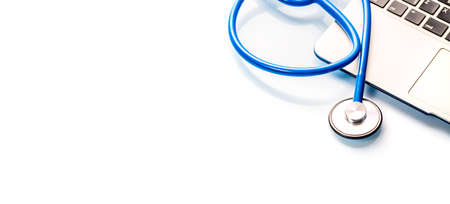 Top view of professional medicinal stethoscope lying on premium gray laptop on blue background
