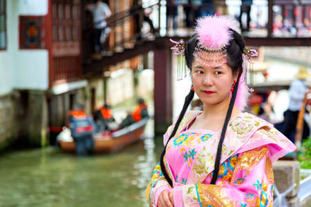 Shanghai, China - May, 2019: Chinese beautiful asian woman in national dress against Shanghai Zhujiajiao ancient Town in Shanghai, China. Chinese Venice
