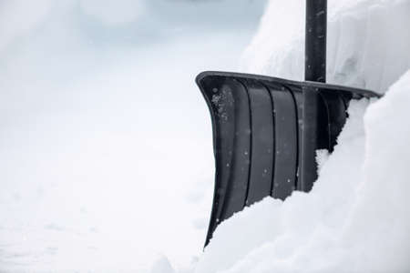 Snow cleaning concept. Black shovel in snow after snowfall.