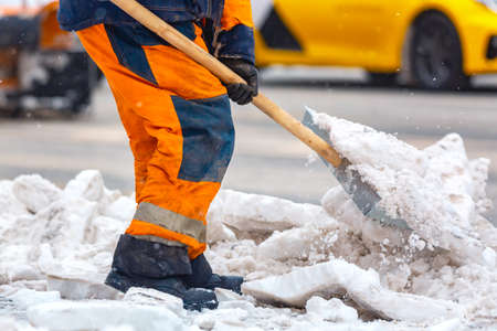 Communal services worker sweeps snow from road in winter, Cleaning city streets and roads during snowstorm. Moscow, Russia