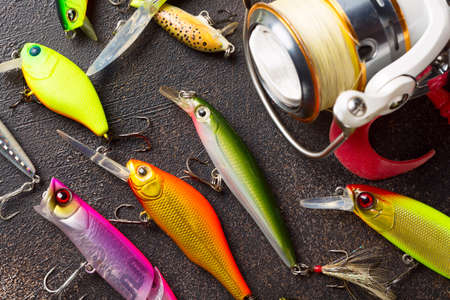 Fishing spinning reel and wobblers. Fishing background.
