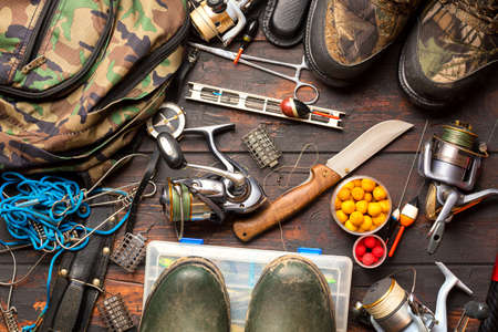Fishing accessories. Frame with fishing boxes, reels, fishing floats, rod, compass, feeder, knife, fishing boots and fish string on wooden background