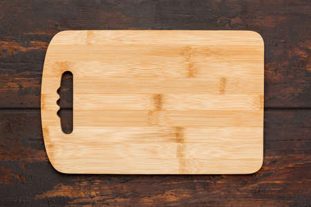 New rectangular bamboo wooden cutting board on wooden table. Top view. Mock up for food project