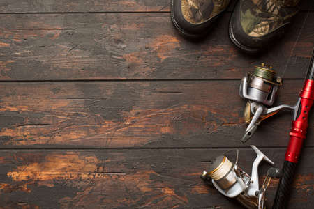 Fishing concept. Fishing spinning rod, reels with lines and fishing boots on wooden background with free space Фото со стока