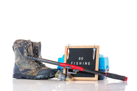 Go fishing concept. Box, rod with reel, fishing boots and black letterboard with words go fishing and fishing lures isolated on white background. Фото со стока