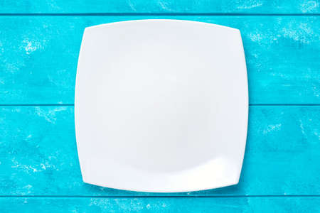 Empty white plate on blue wooden table. Top view. Mockup for food project