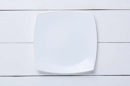 Empty white plate on white wooden table. Top view. Mockup for food project