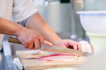 chef cleaning a fish to cook 写真素材