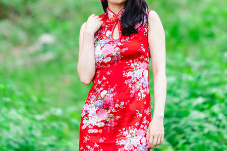 a woman in a Chinese dress standing in the woods Stok Fotoğraf
