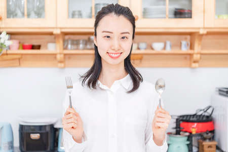 Woman with fork and spoon in the kitchen 写真素材