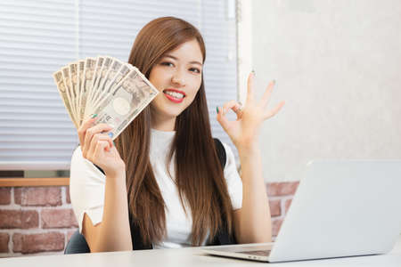 Young woman holding money shot in the studio