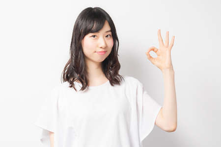 Young woman making an OK gesture 写真素材