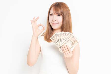 Woman wearing a dress holding money taken in the studio