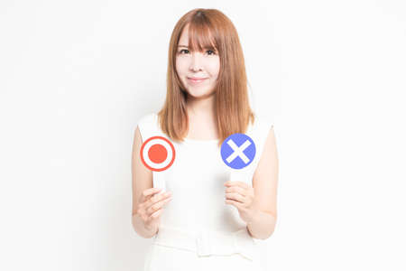 Young woman with OK and NG placard shot in the studio 写真素材
