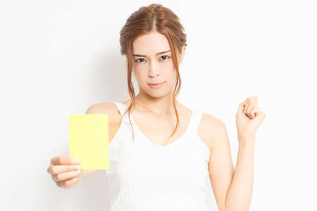 Young woman holding a yellow card in her hand