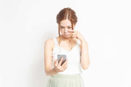 A young woman holding a smartphone Standard-Bild