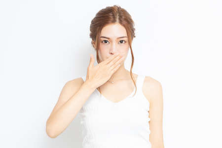 Young woman putting her hand on mouth