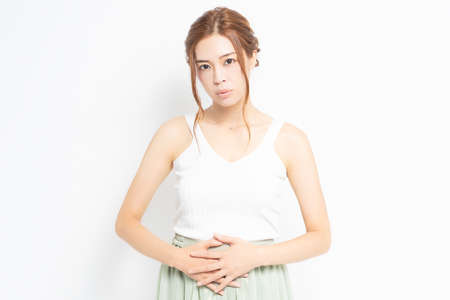 Young woman dressed in white putting hands on her stomach