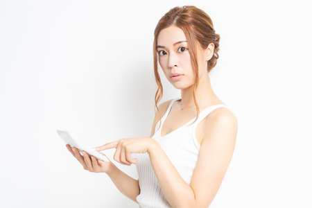 Young woman using a calculator shot in the studio
