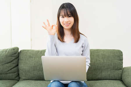 Young young woman sitting on the sofa and making an OK sign
