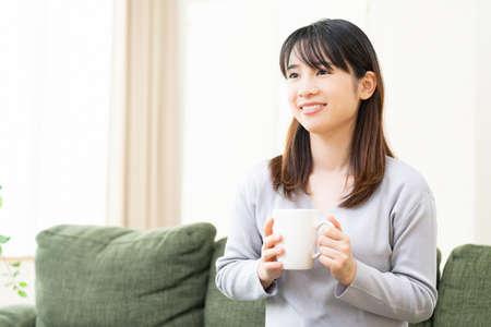 Woman drinking coffee on living room sofa