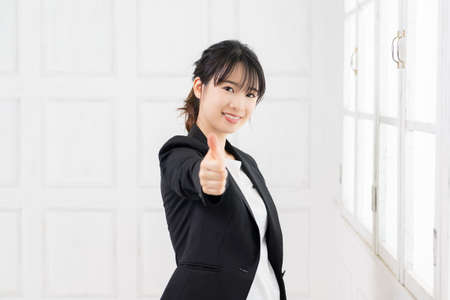 Young business woman making a gesture of like shot in the studio