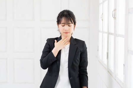 Young business woman with a sore throat taken in the studio
