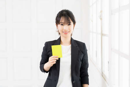 Young business woman holding a yellow card in her studio shot
