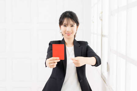 Young business woman holding a red card in her hand taken in the studio