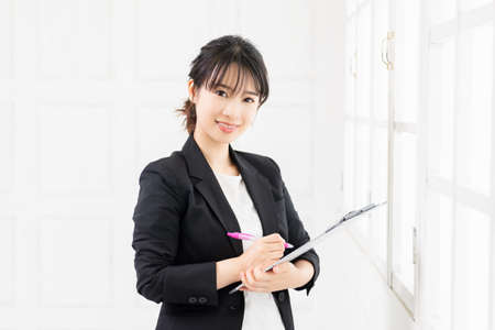 Young business woman recording on clipboard shot in studio